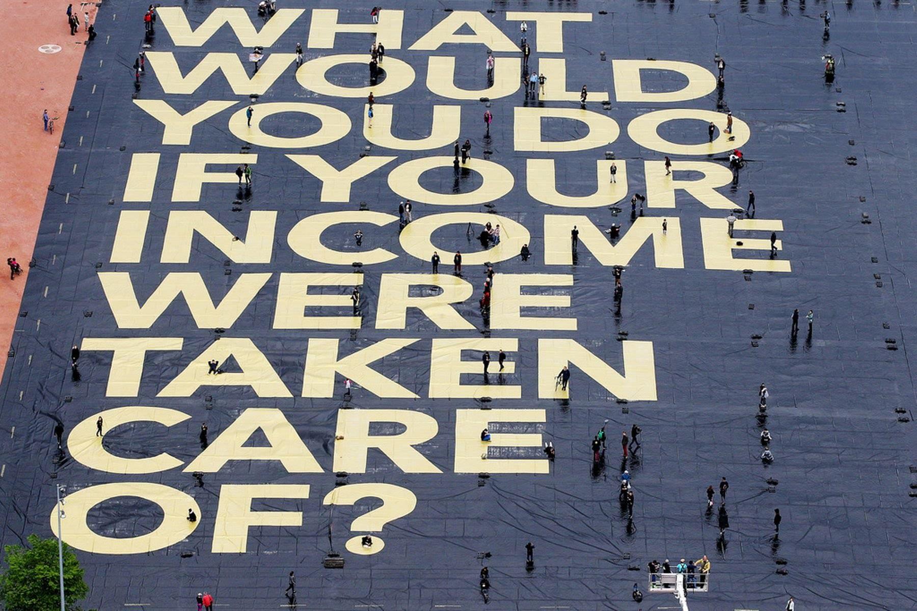 """""""Cosa faresti se non ti dovessi più preoccupare del tuo reddito?"""" - Megaposter da Guinnes dei primati installato a Ginevra nel maggio 2016 - Fonte http://www.bin-italia.org/"""